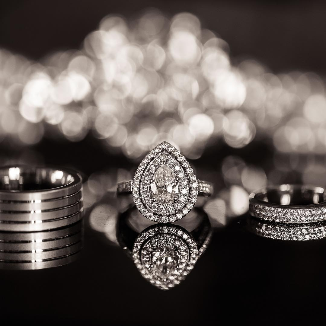 Detail photo of three wedding rings placed on a black reflective surface with a bokeh background