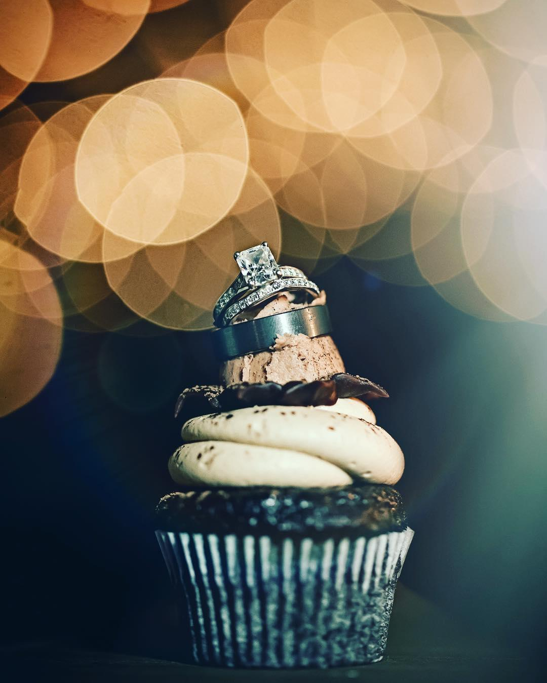Two wedding rings placed on top of a chocolate cupcake with cream frosting with a bokeh effect background