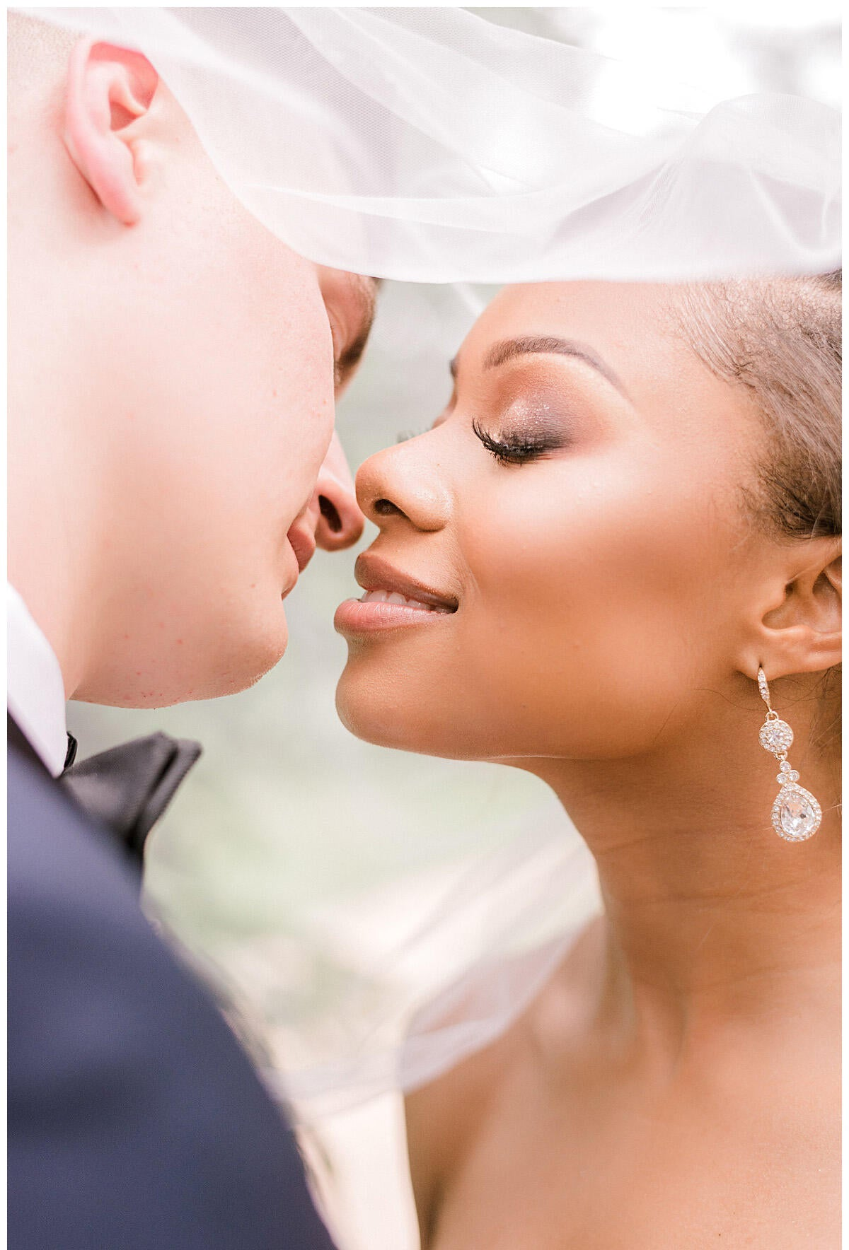 bride and groom almost kissing under veil