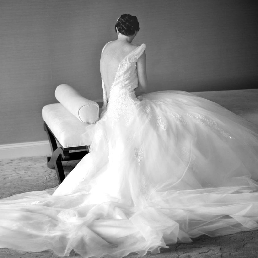 Black and white image of a bride getting ready and putting on her wedding dress
