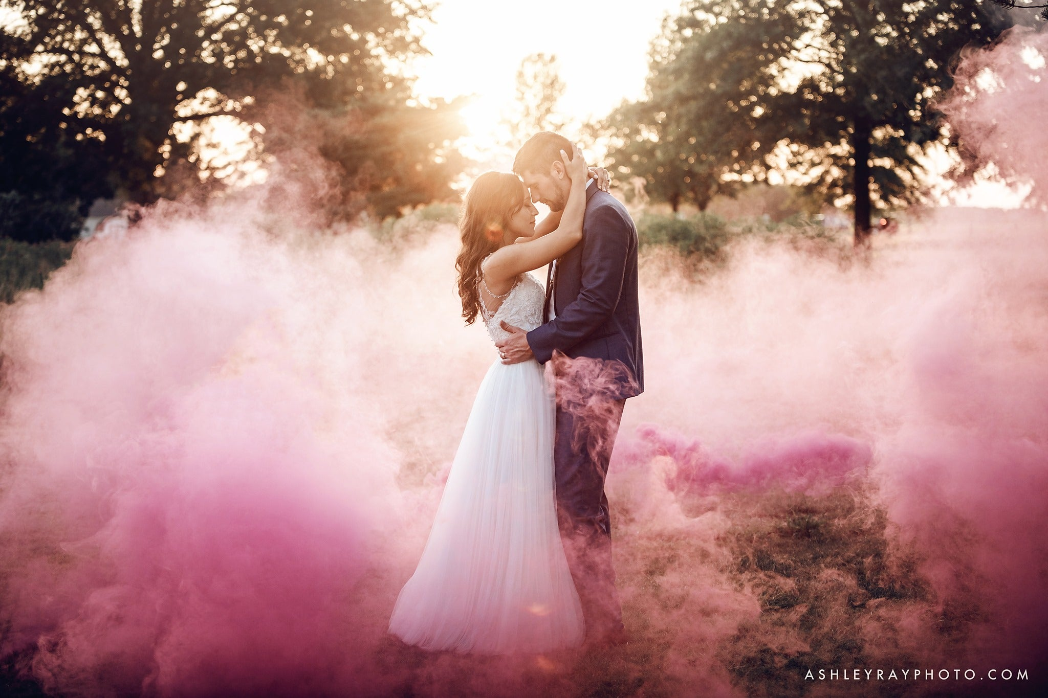 Bride and groom holding each other as a cloud of pink color smoke bomb surrounds them