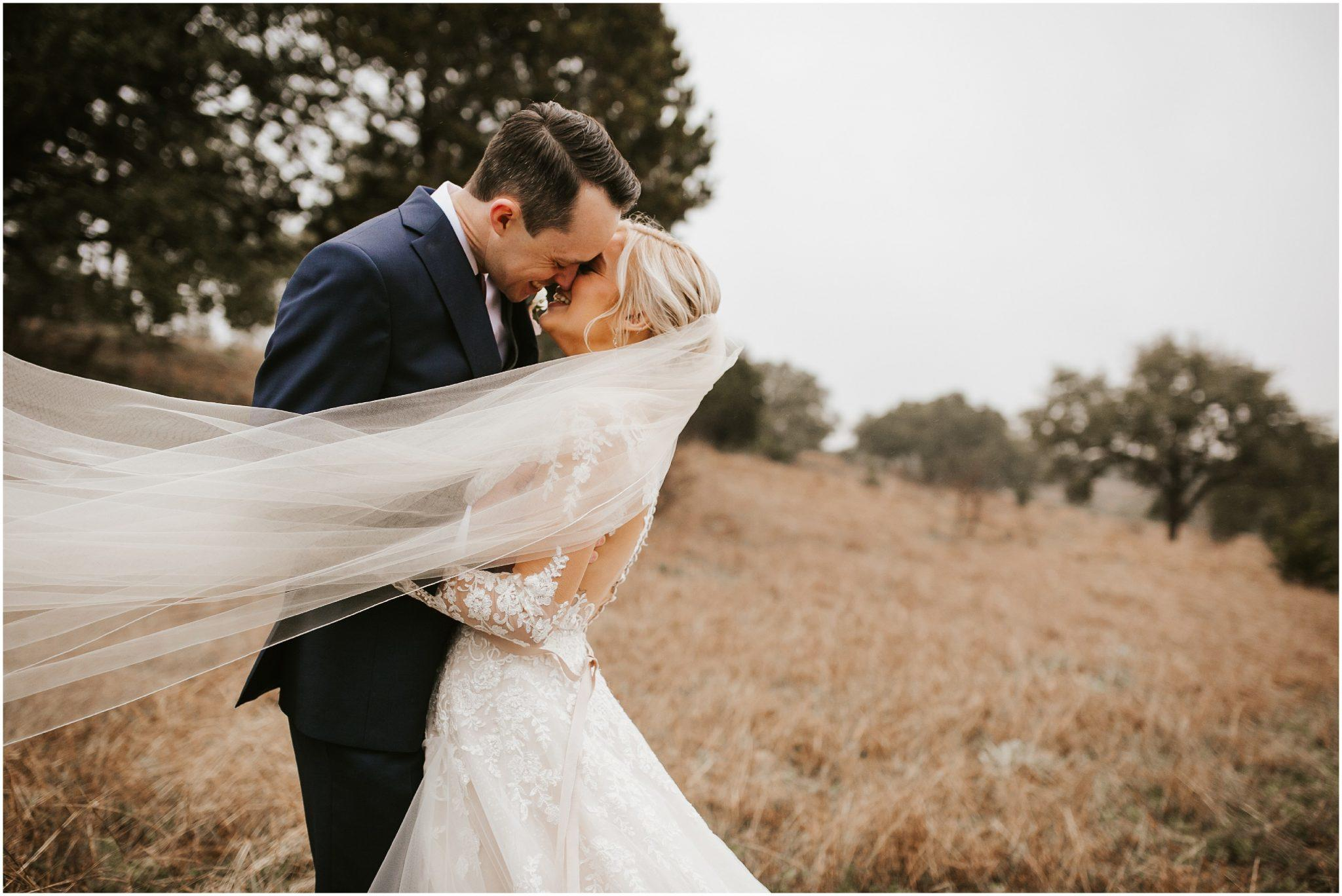 couple kissing and smiling in wedding attire in a brown grassy field