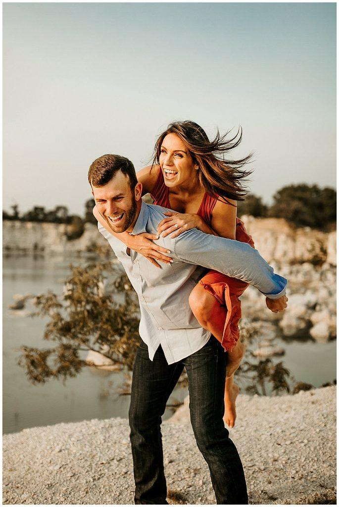 woman getting a piggyback ride from man while laughing near water by Brandi Allyse Photography
