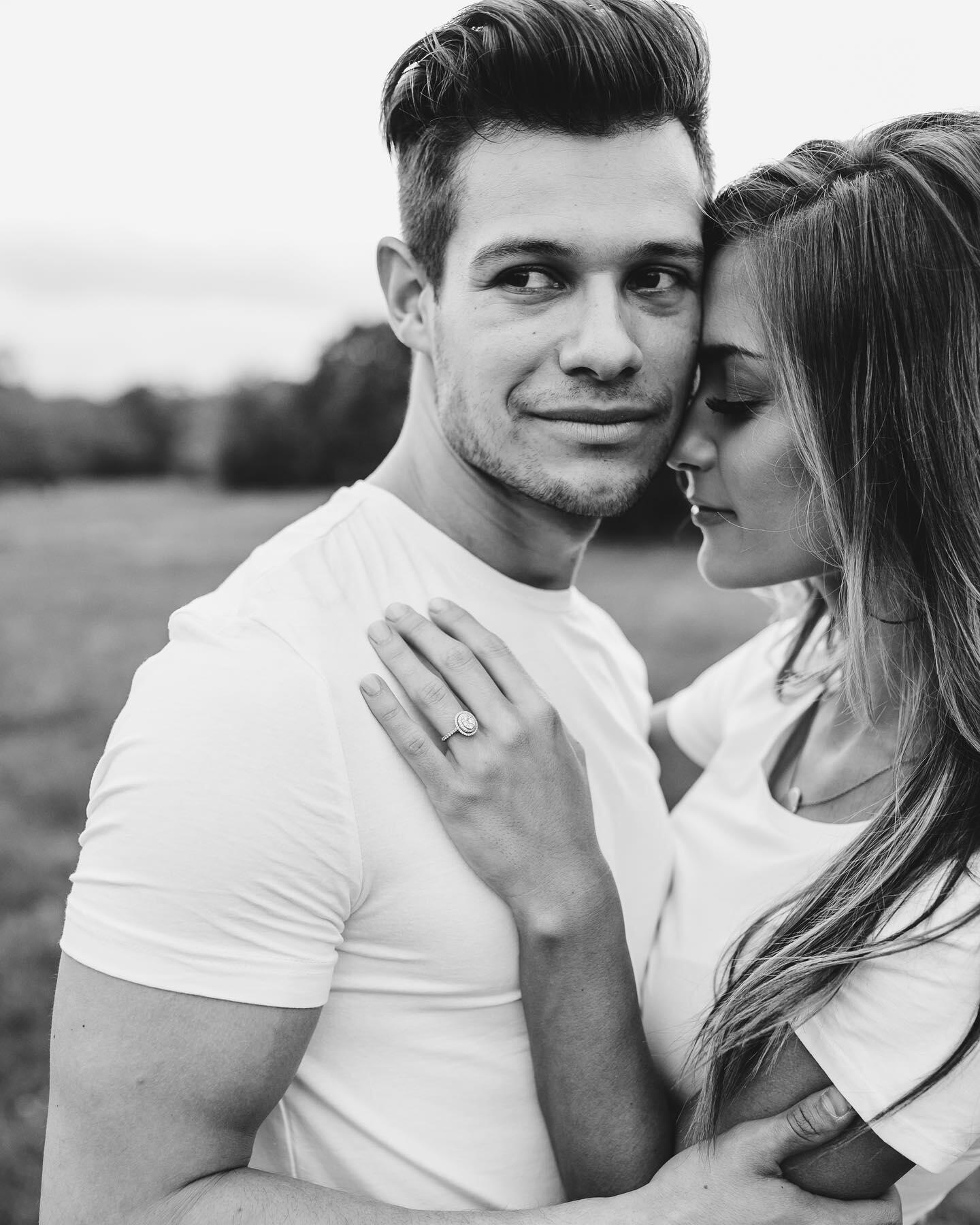 Black and white portrait of a couple holding each other with the girl resting her hand on the guy's chest