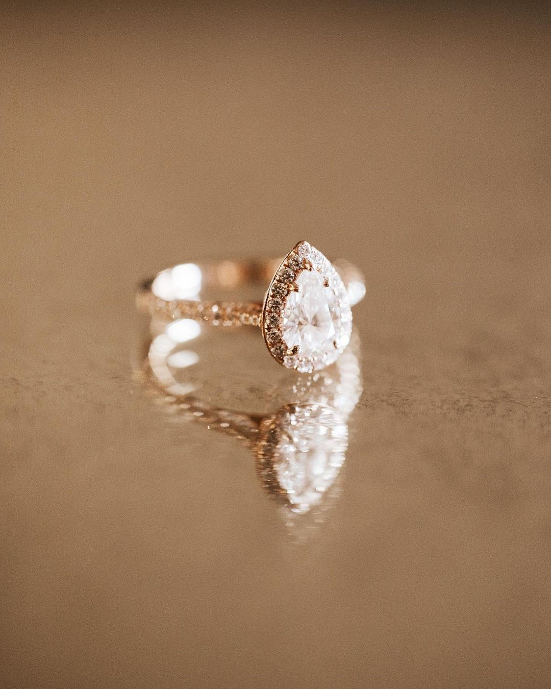 A pear-shaped wedding ring placed on a reflective surface