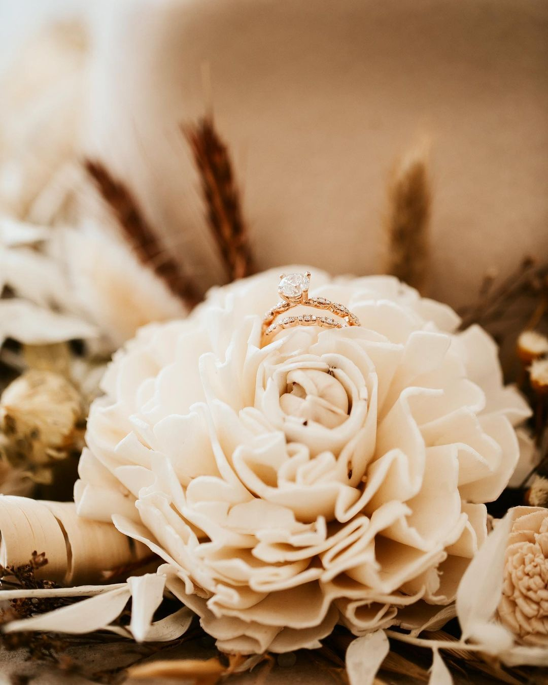 Close up shot of a wedding ring placed on top of an artificial white color flower