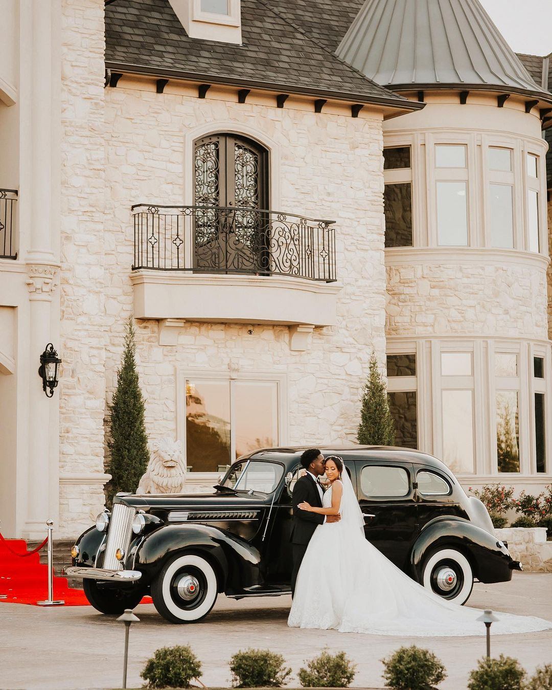 Bride and groom posing in front of a black car in front of a castle-themed building