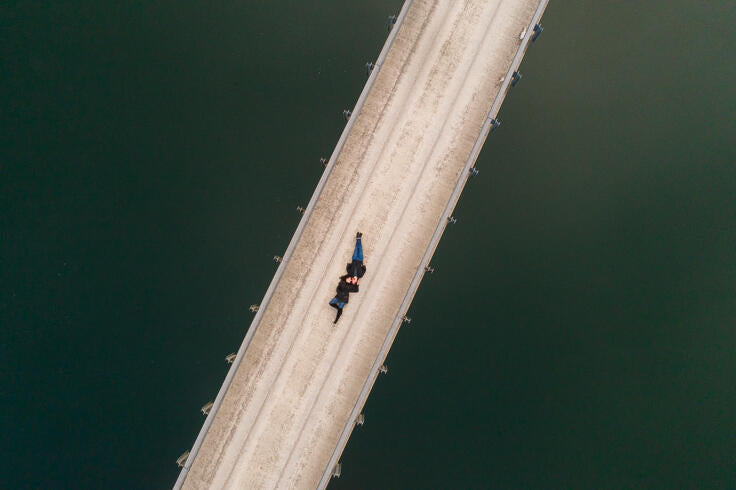drone photo of couple laying on cream road in green water