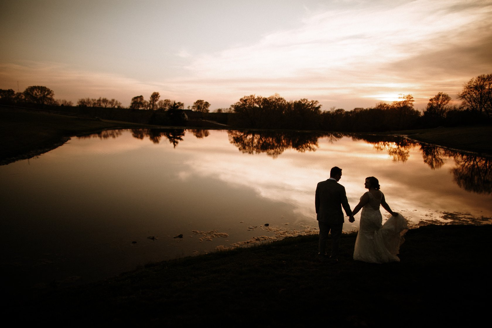 A bride and groom holding hands and posing in front of a lake during sunset