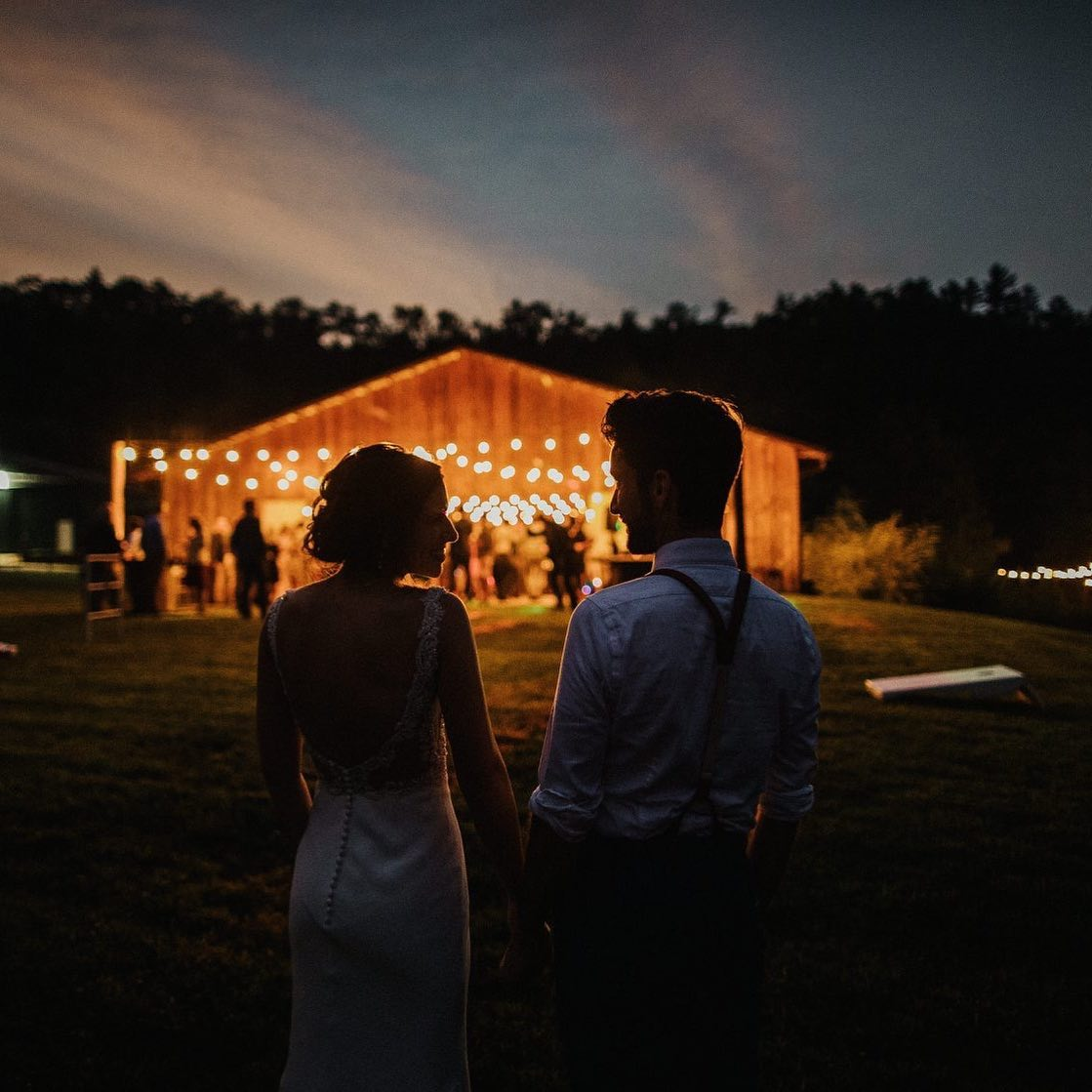 Silhouette of a bride and groom holding hands in front of the wedding venue