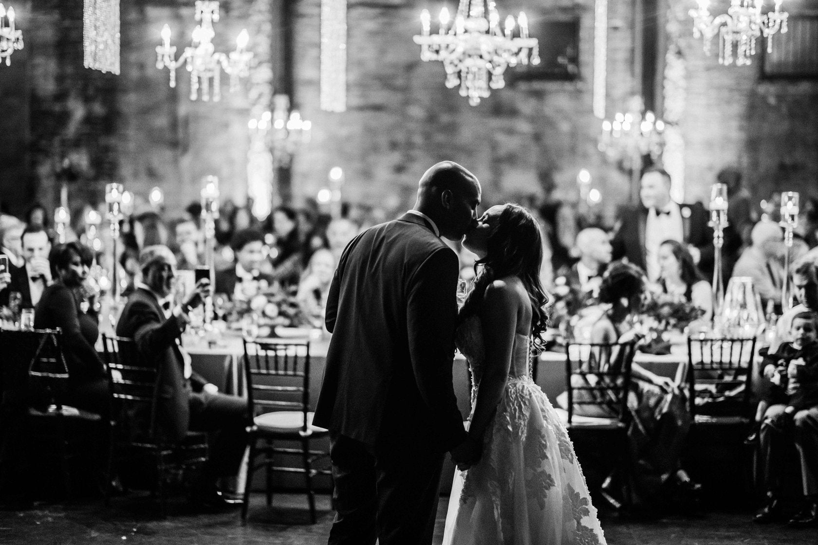 Black and white image of the bride and groom hold hand and kiss as the guests watch over from the dinner table