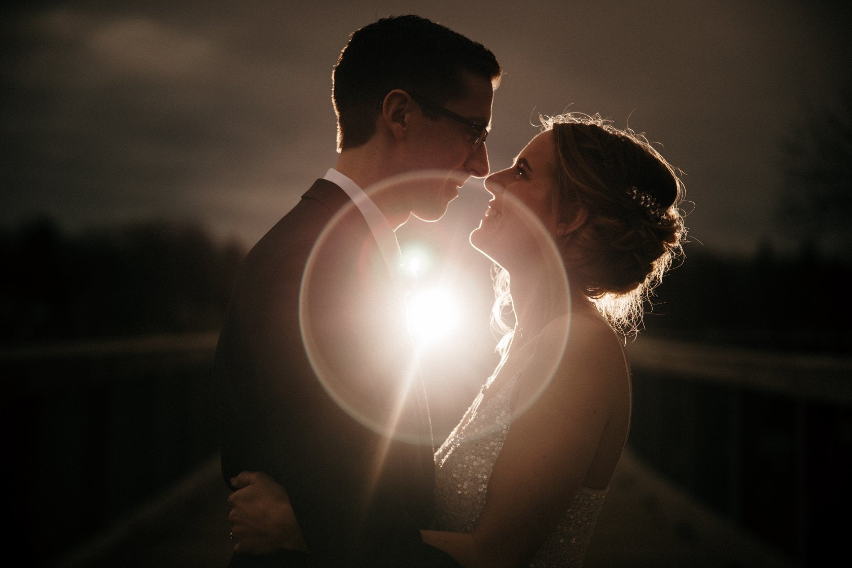 Portrait of a bride and groom looking at each other as the lens flare creates a halo effect in between them