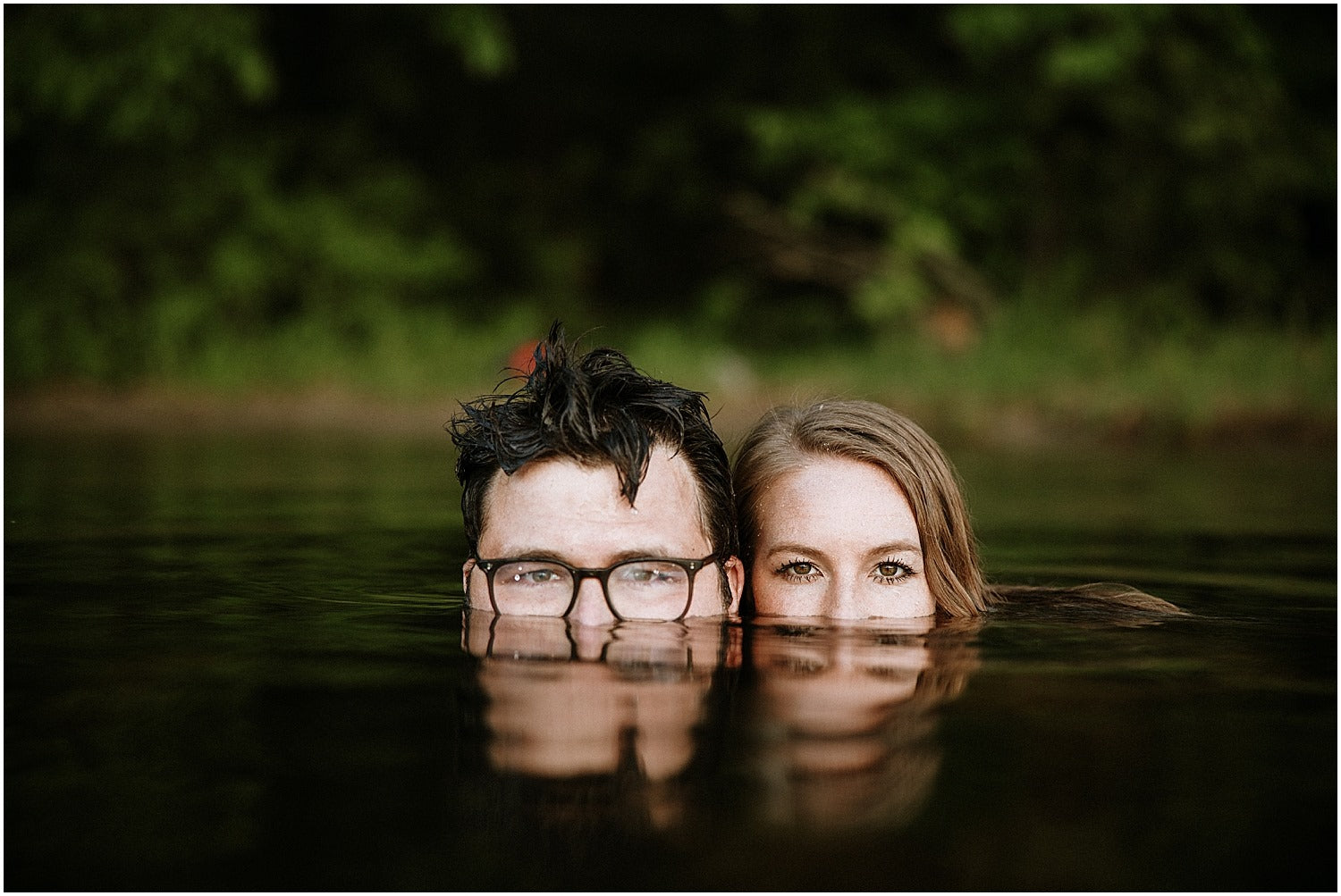 Couples posing from a lakeside with only half heads above the water