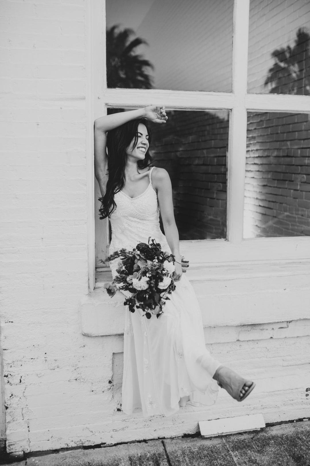 Black and white photo of a bride holding a bouquet while posing in front of a window