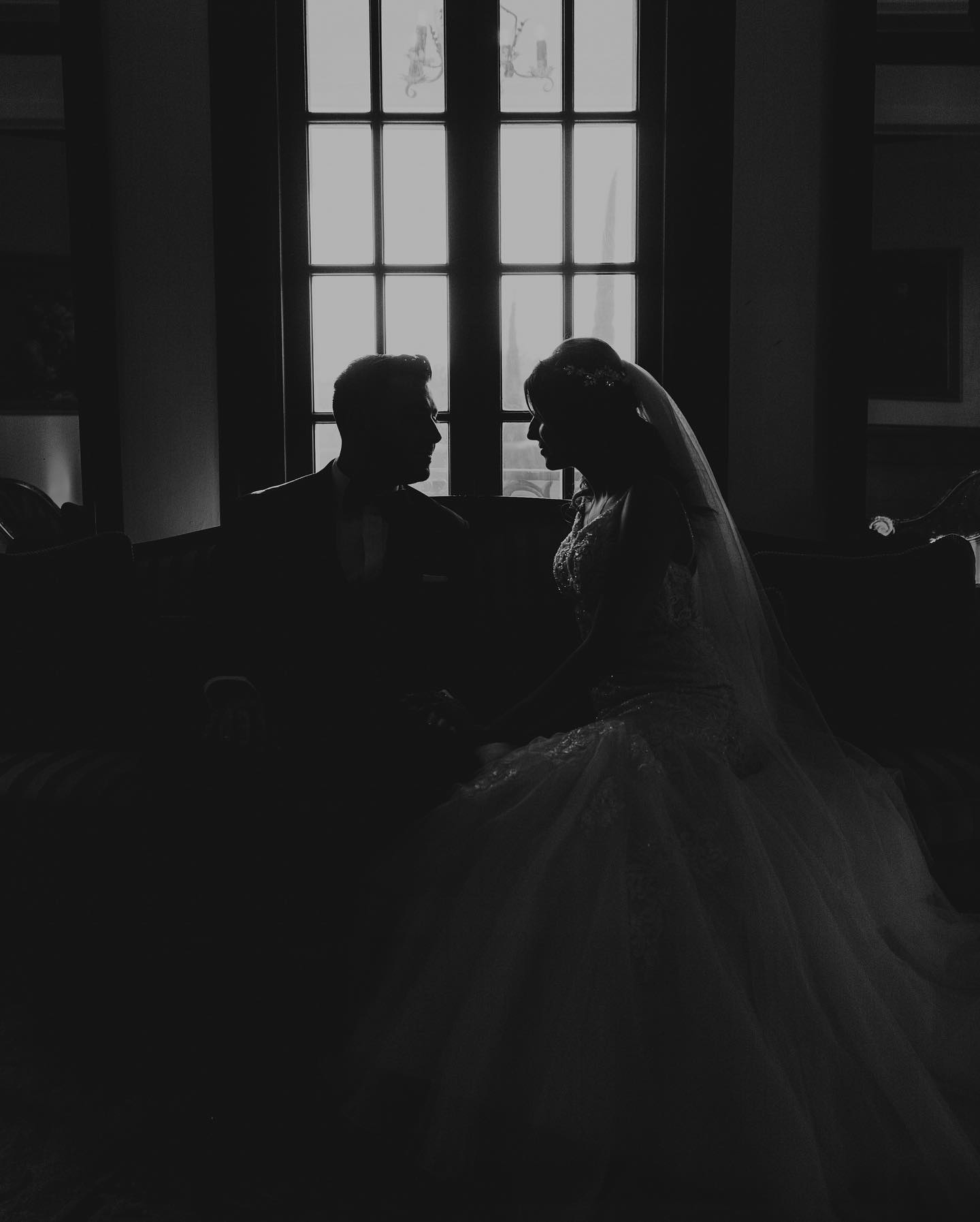 Black and white silhouette of a couple sitting on a couch facing each other