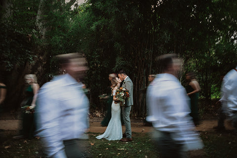 Bride and groom kissing at an open space with bridesmaid and groomsmen acting as a blurred frame