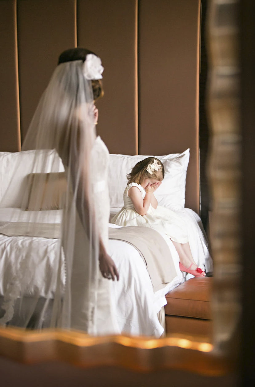 The bride watches over the flower girl sitting on the bed with hands placed over her eyes
