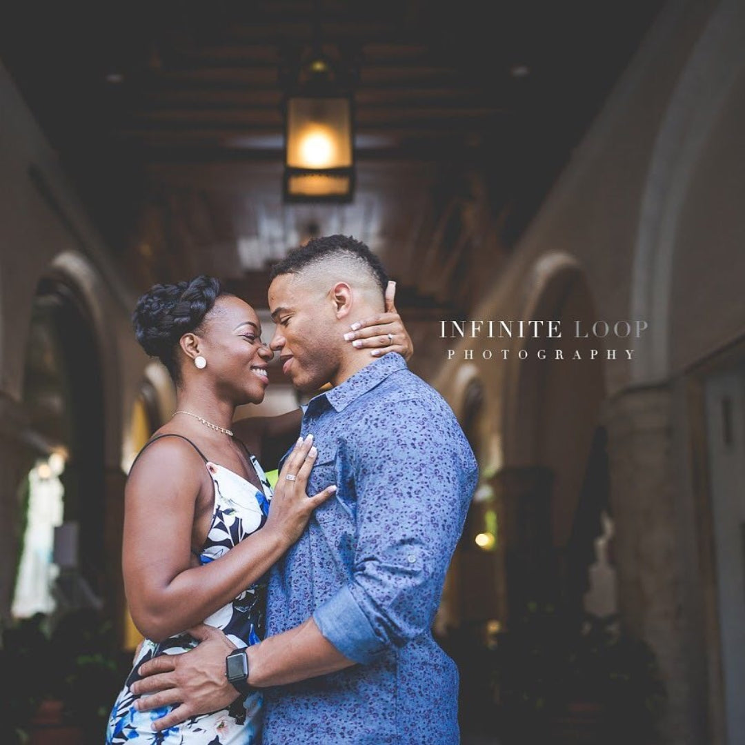 A couple of color holding each other and posing for an engagement session