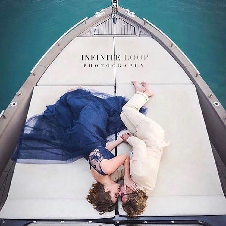 woman in blue dress with man in white suit laying on a boat