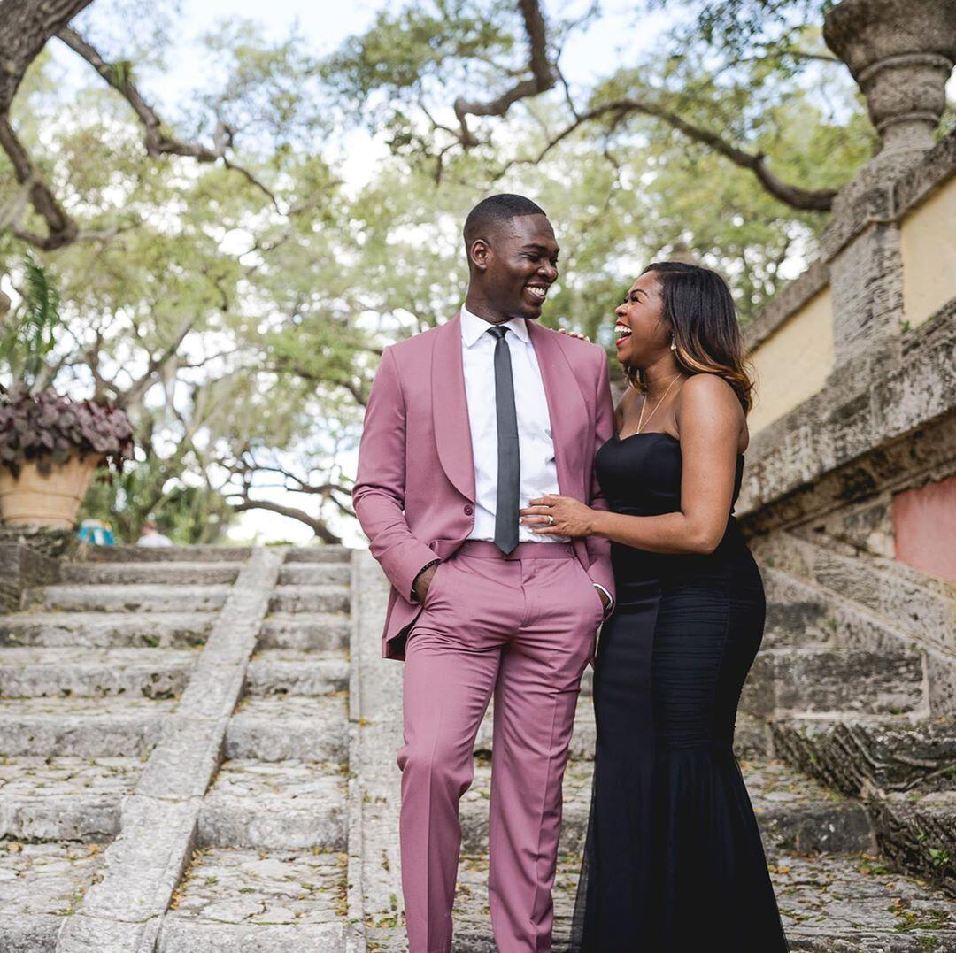 black couple in a suit and formal black dress laughing at each other