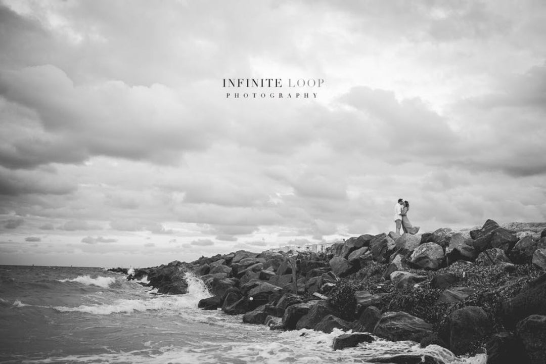 Black and white photo of a couple kissing on top of a cliff as the waves crash on the rocky shore