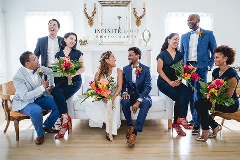A bride and groom sitting at the center of the couch while the bridesmaid and groomsmen surround them