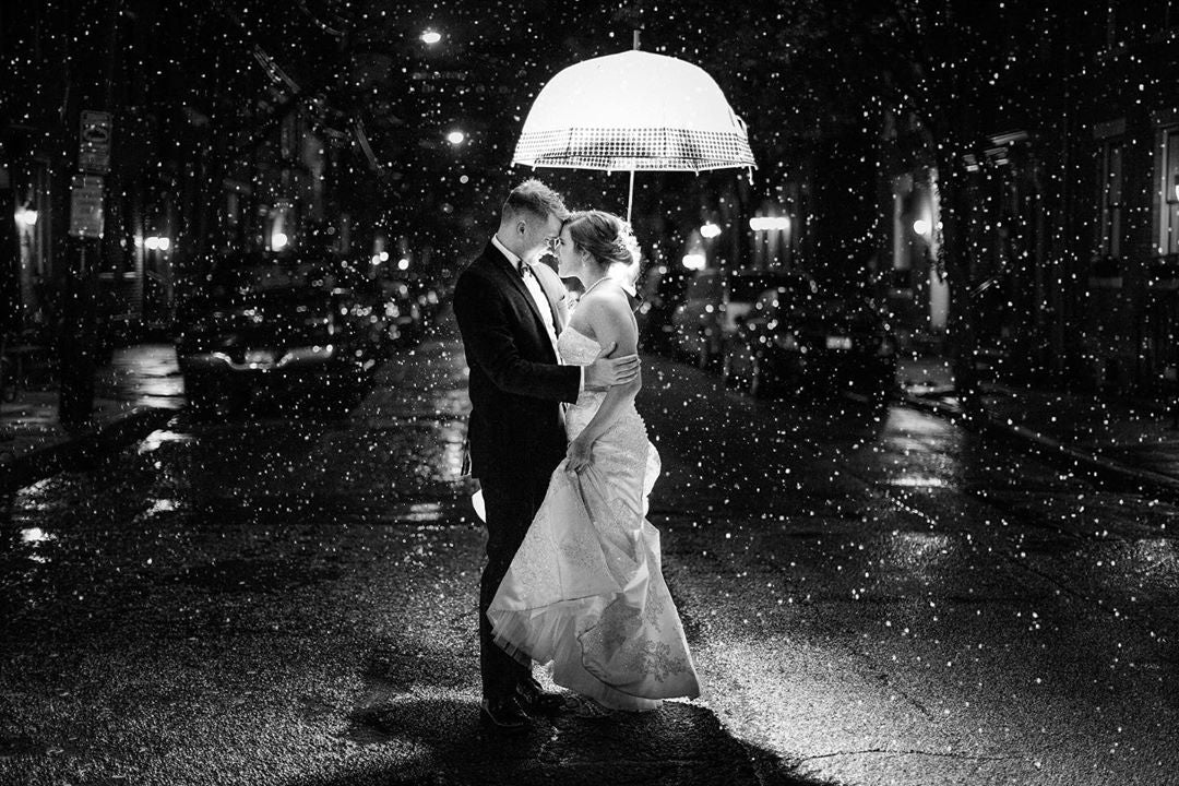 Bride and groom posing under an umbrella as the rain creates a beautiful background