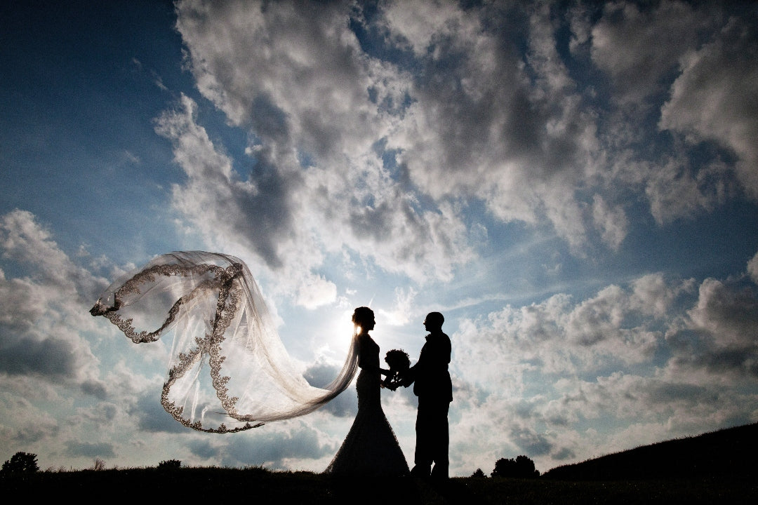 Silhouette of a bride and groom holding the bouquet with bride's veil flowing in the air