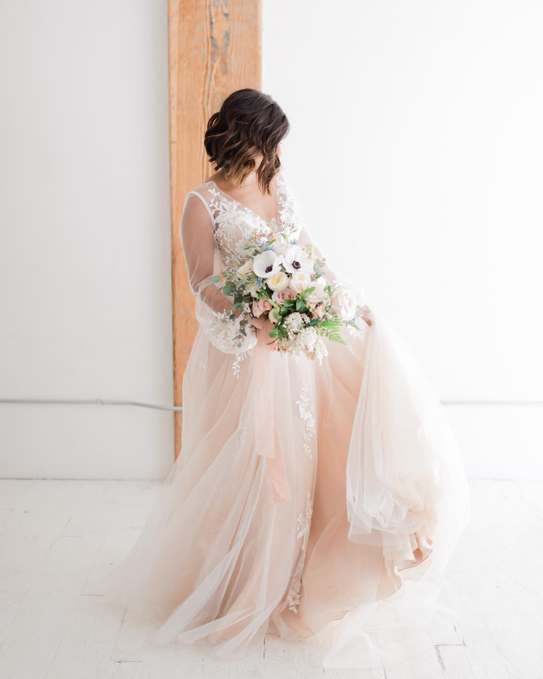 Full-body portrait of a bride posing with the bouquet