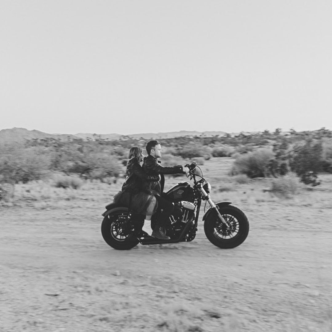 Black and white photo of a couple riding a motorcycle on a dirt road