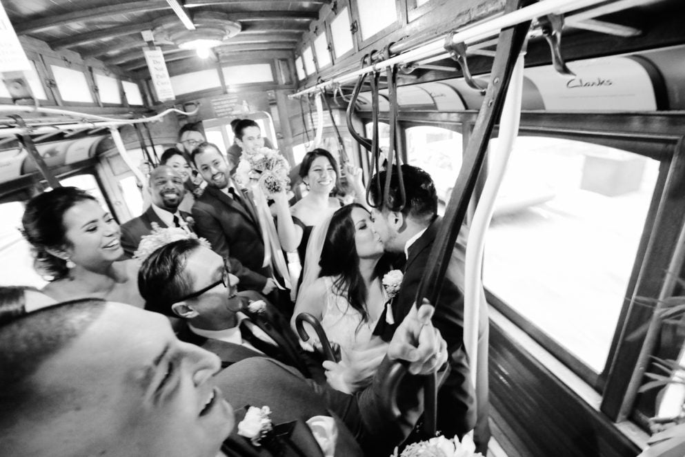 Bride and groom share a kiss on a subway as the guests surrounding them cheer with joy