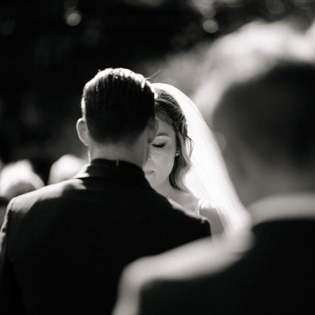 Black and white portrait shot of a bride taken from over the groom's shoulder.