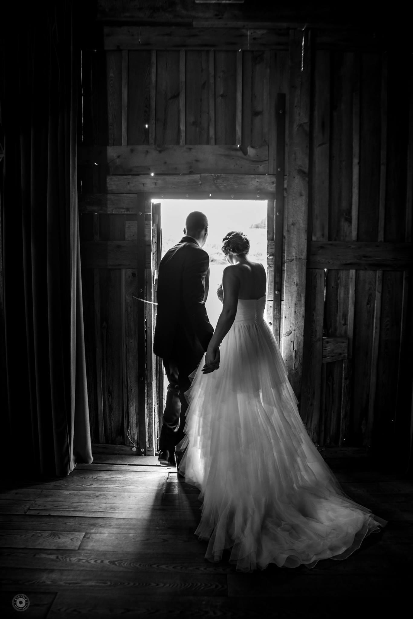 couple walking through doorway of a barn from dark inside to light outside