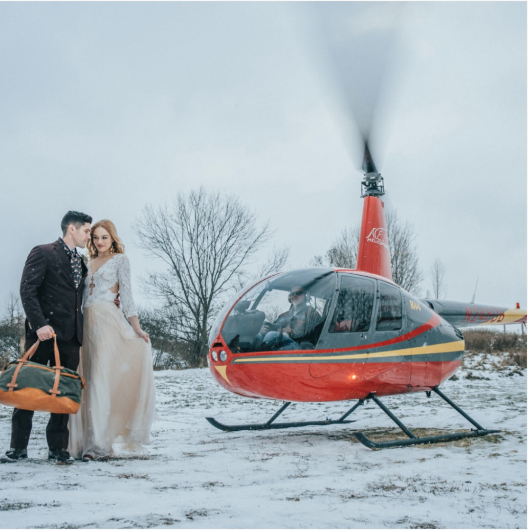 A bride and groom posing in front of a helicopter