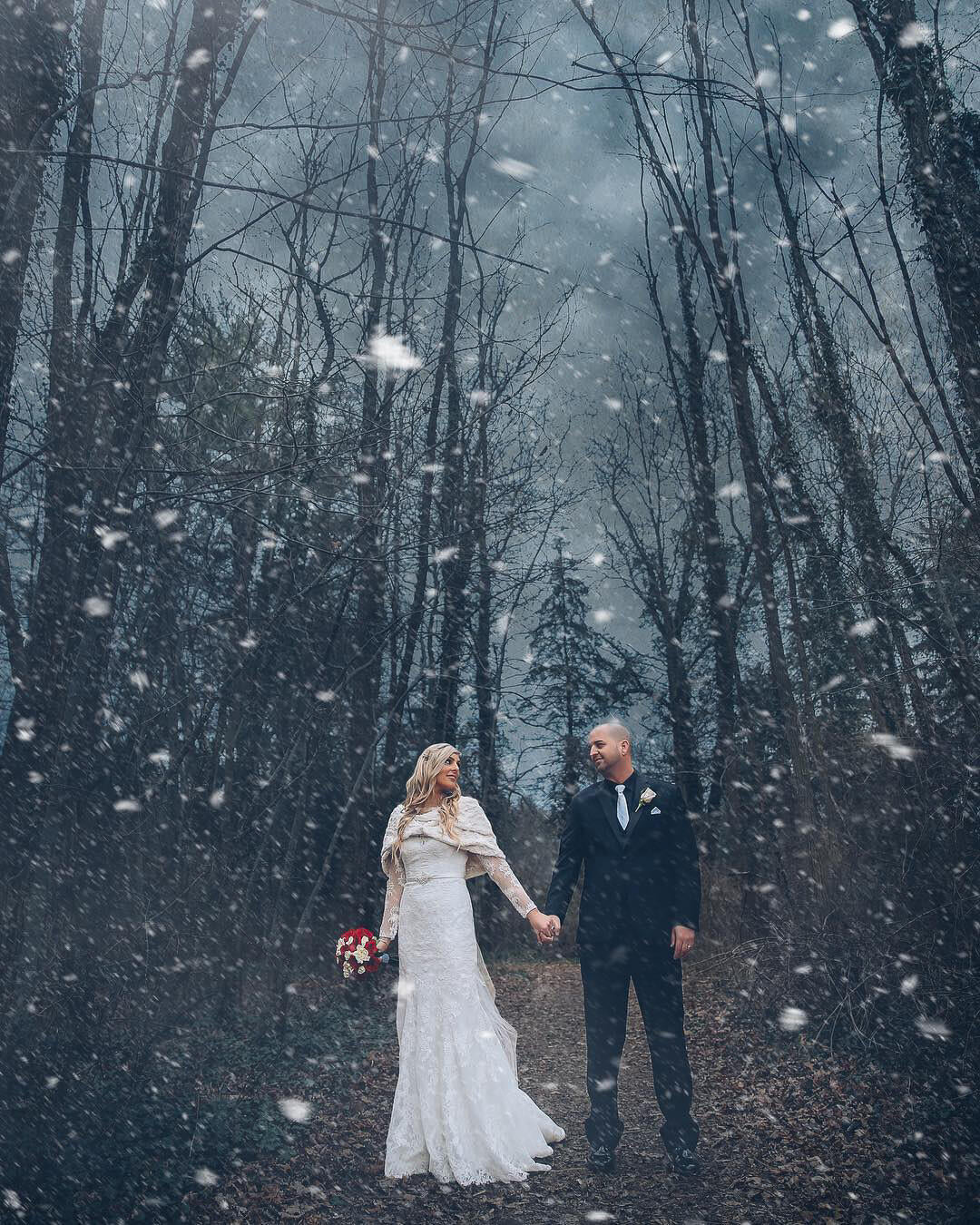 A winter wedding photoshoot of bride and groom walking hand-in-hand  during the snowfall