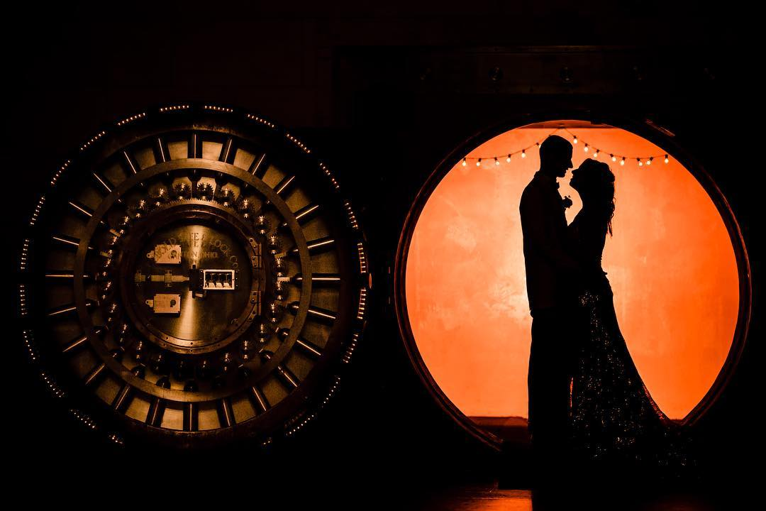 Silhouette of a couple looking at each other as they stand under a circle shaped doorway