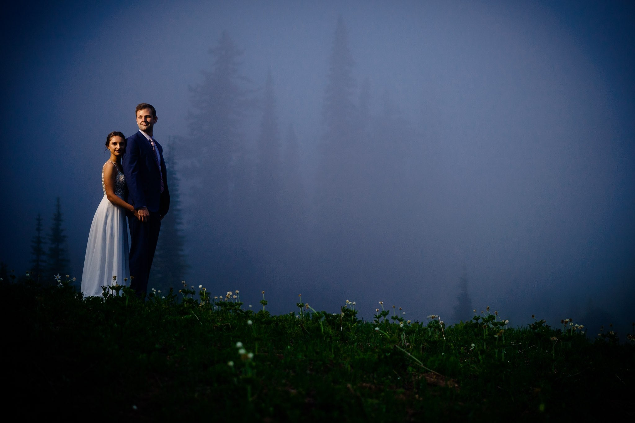 Bride and groom posing in a dark and moody outdoor setting