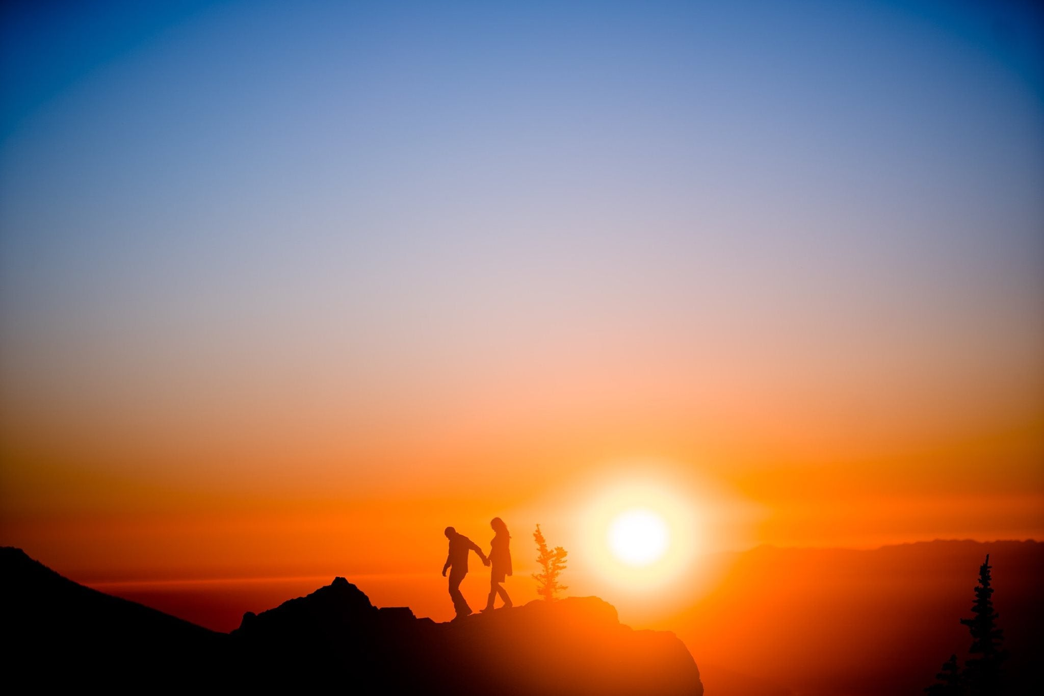 Silhouette of a couple walking holding hands on top of a cliff as the sun sets behind them