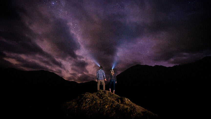 couple standing on a rock during a starry night wearing headlamps