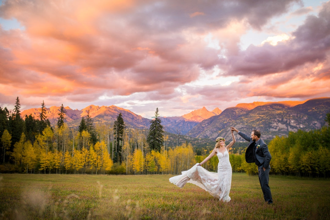 Bride swirling while holding the train of her dress from one hand and the groom's hand from the other in a natural setting