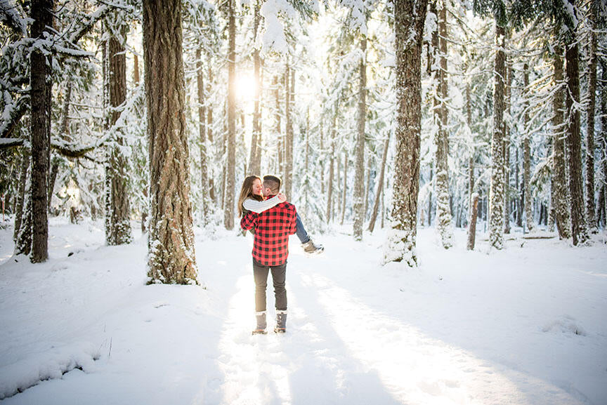 man carrying woman in a snow covered forest at sunset