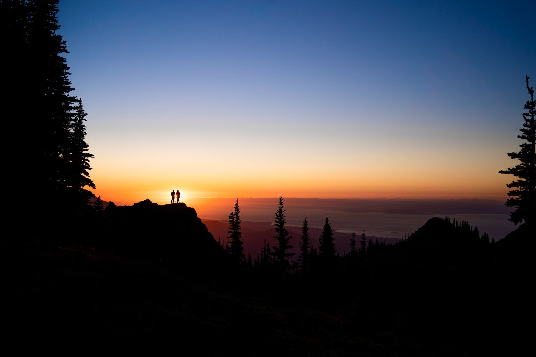 Silhouette of a couple standing on top of a cliff as the sun sets behind them