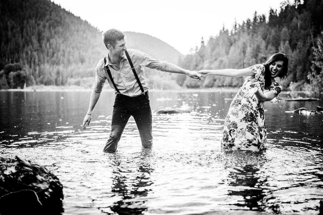 Black and white photo of a couple standing in knee-deep lake water while splashing water at each other