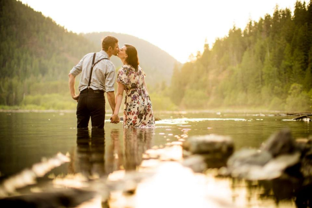 A couple kissing and holding hands while standing knee deep in lake water