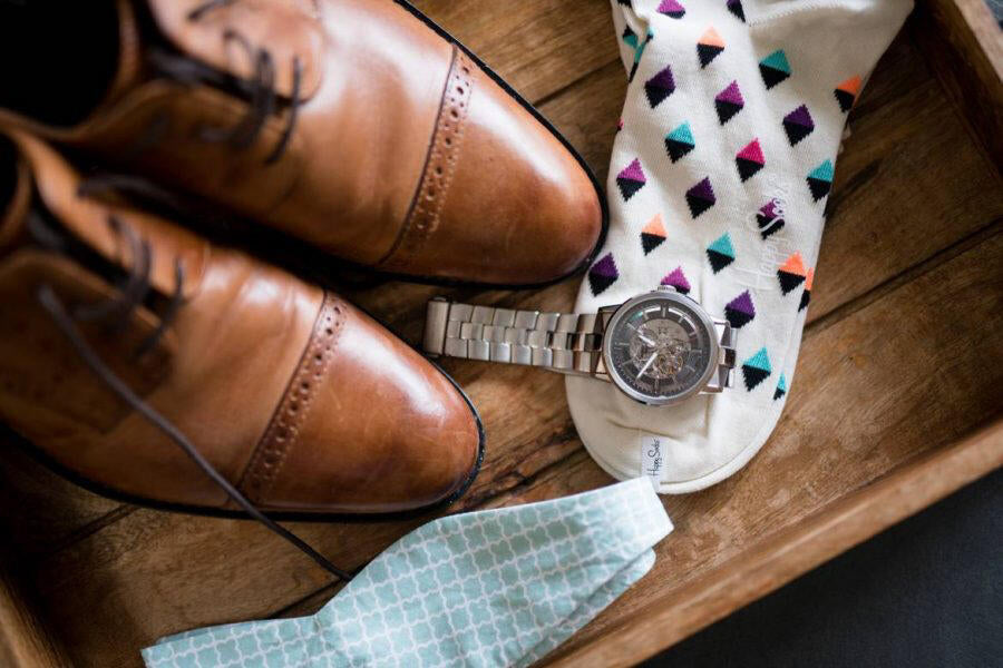 close up of shoes, watch, socks and bowtie on wedding day