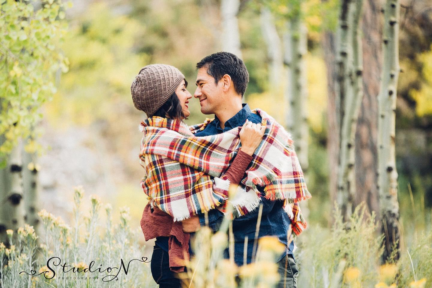 couple cuddling under a plaid blanket in the fall