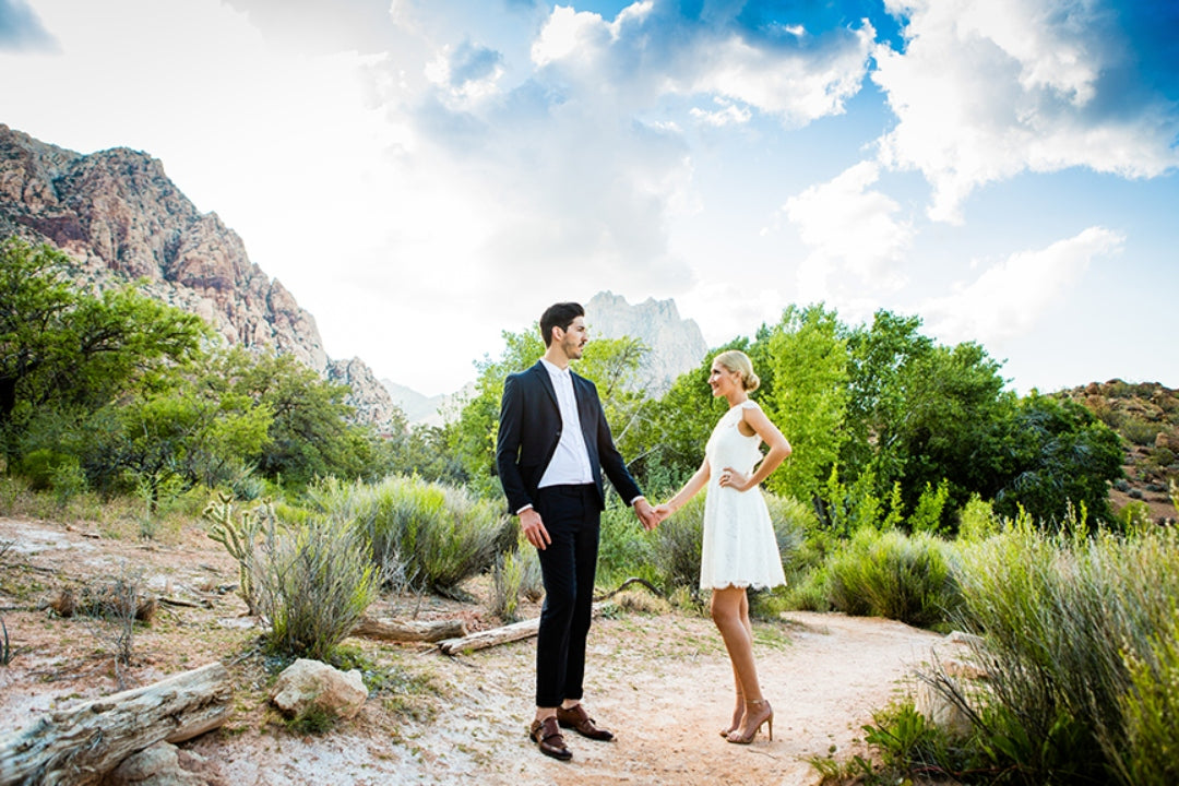 A couple posing at an outdoor setting while holding hands
