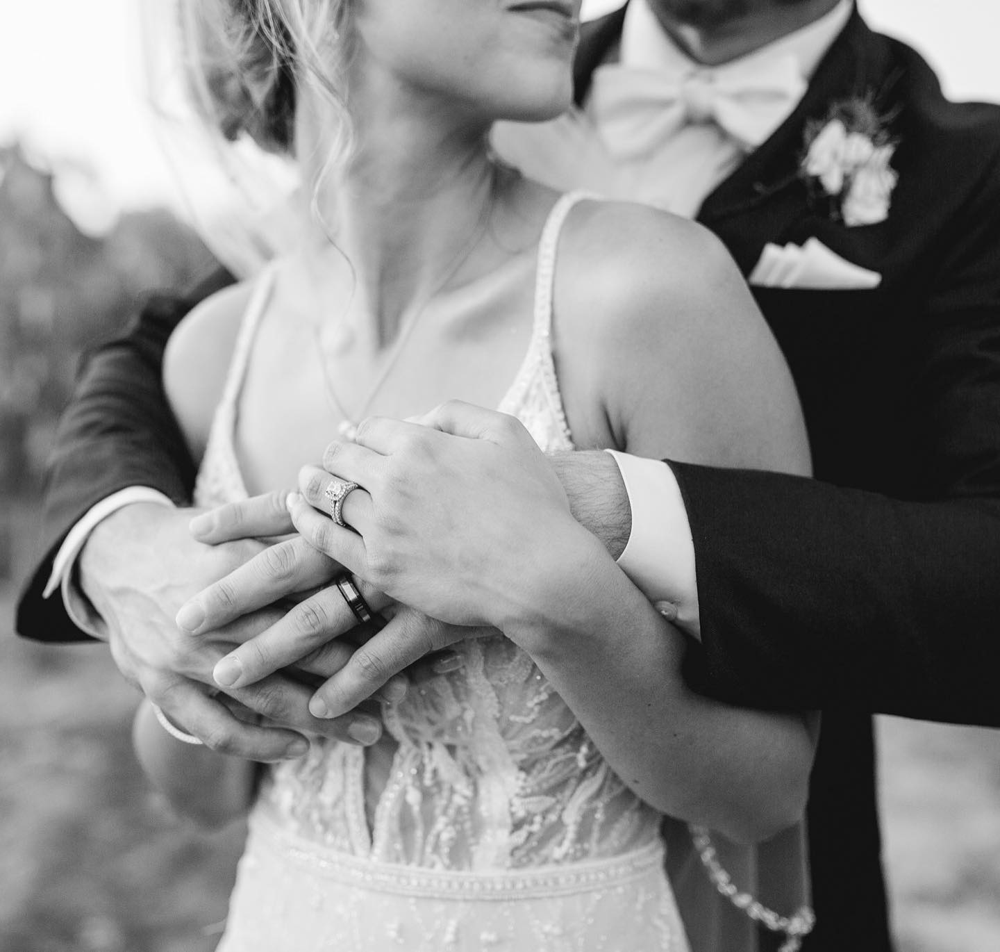 Black and white portrait of a couple showing their rings as the groom hugs the bride from the back and the bride holds his hand