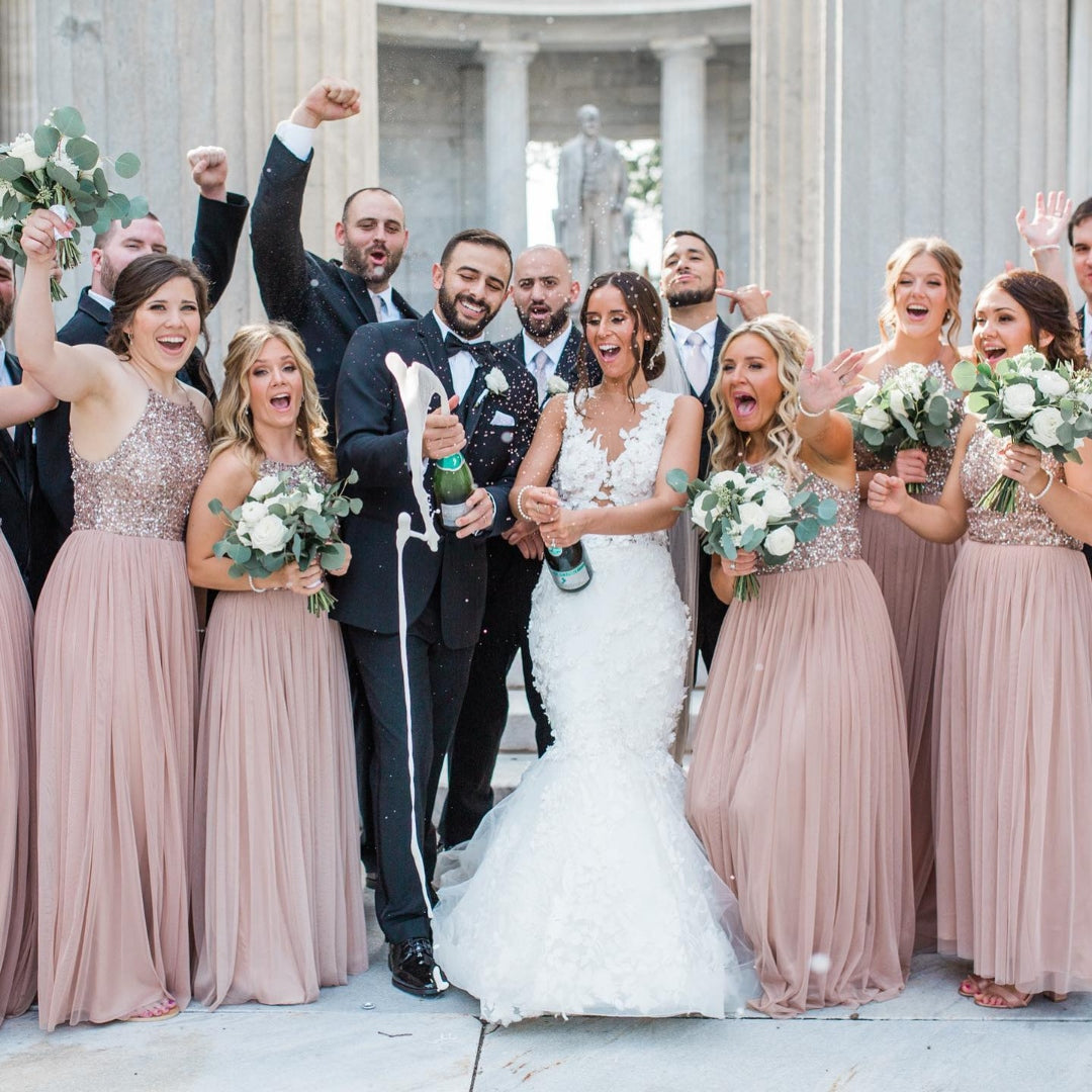 Bride and groom popping open the champagne bottle while being surrounded by bridesmaids and groomsmen