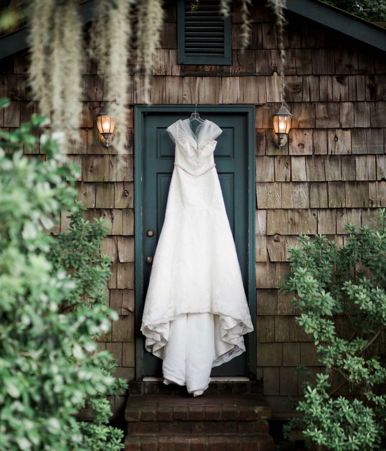 A bride's wedding dress placed on a hanger in front of a blue colored door